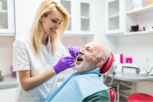 The dentist carefully cleans the patient's teeth.
