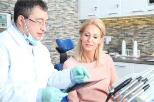 The dentist explains the X-ray result to the patient.