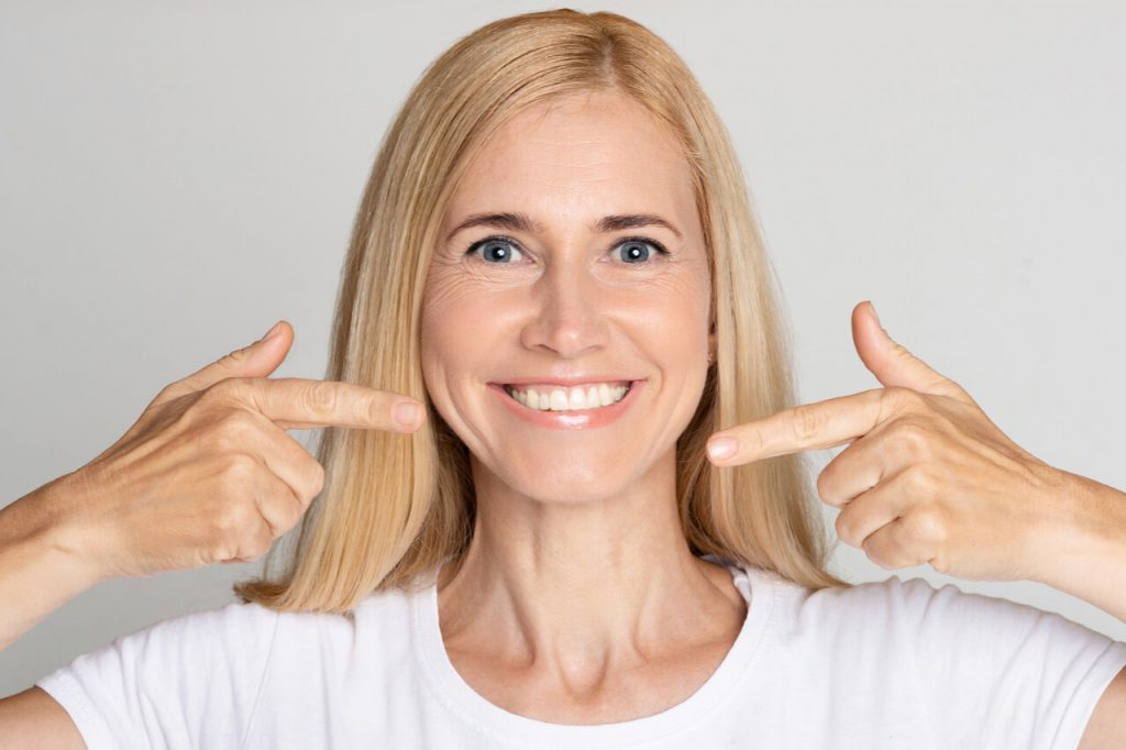 The woman has successful dental implants.