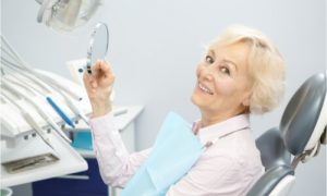 The woman knows how much do full dental implants cost.